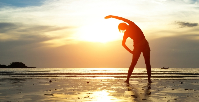 Silhouette young woman, exercise on the beach at sunset.